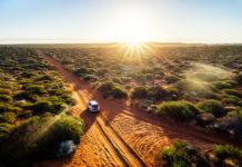 Luftaufnahme vom australischen Outback mit Auto während Sonnenuntergang