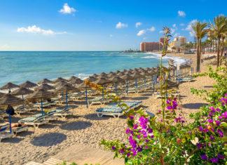 Der Strand von Benalmadena mit Liegebetten und Palmen