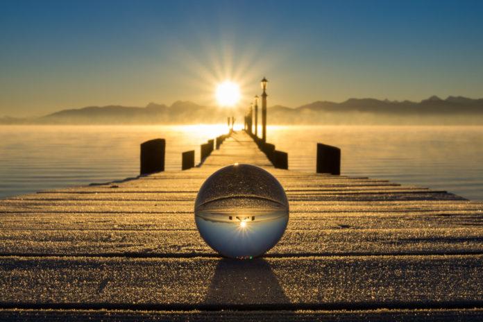 Spiegelung eines Stegs in einer Glaskugel bei Sonnenuntergang