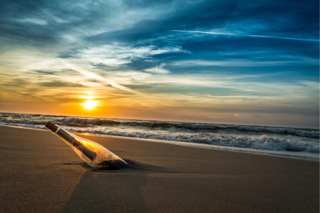 Flaschenpost bei Sonnenuntergang im Strand
