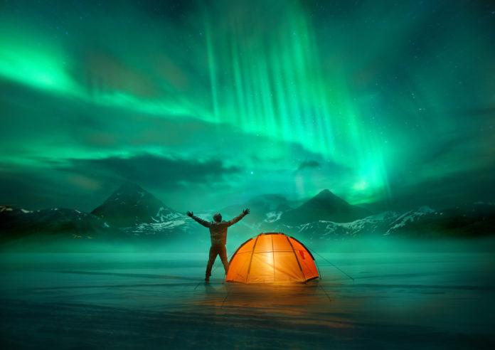 Camper mit seinem Zelt in Island unter Nordlichtern