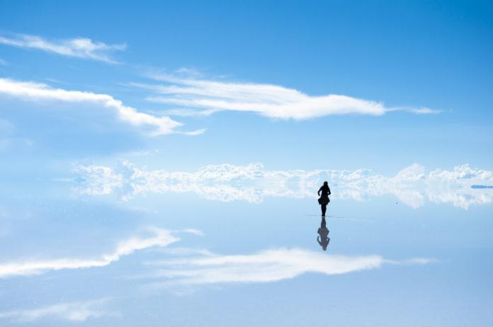 Der Salzsee von Uyuni mit der Spiegelung eines Mädchens
